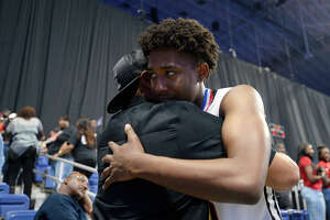 Memorial's Thailan Wesley hugs Therrin Juneau, his former youth basketball coach, after beating Northwest in the class 5A state final at the Alamodome in San Antonio on Saturday afternoon.   Photo taken Saturday 3/10/18 Ryan Pelham/The Enterprise