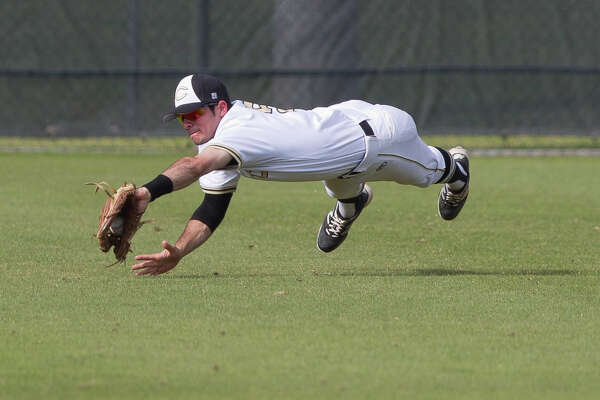 Conroe left fielder Charles Dinaso (5) makes a diving play on Tomball Memorial Alex Quarfordt's line drive in the first inning of a game during the Klein Tomball Tournament, Saturday, March 10, 2018, in Tomball.