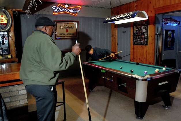 "Neighborhood customers Stafford McGill, left, and Henry ""Birdie"" Wilson shoot a game of pool on Wednesday, Oct. 21, 2009, at the Port Tavern in Albany, N.Y. The brothers-in-law said they've seen Poppy play bouncer some nights, and they've seen him sleeping in the freezing cold next door outside the vacant building. (Cindy Schultz / Times Union) Photo: CINDY SCHULTZ"