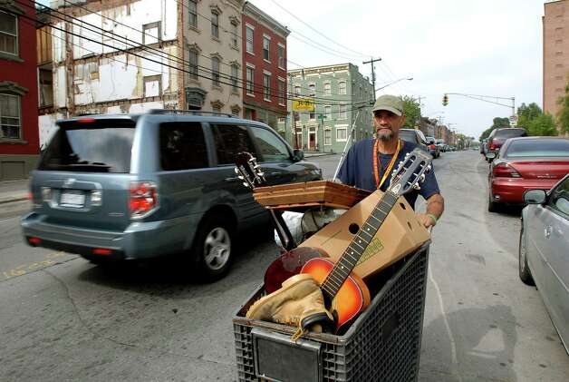 "Samuel ""Poppy"" Baez pushes a shopping cart down Morton Avenue as he moves his belongings from one apartment to another on Tuesday, Sept. 8, 2009, in Albany, N.Y. (Cindy Schultz / Times Union) Photo: CINDY SCHULTZ"