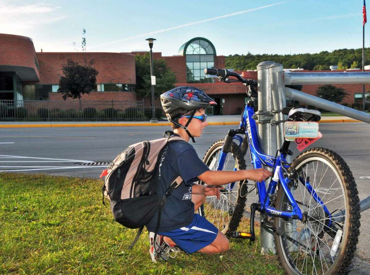 Student Adam Marino, 12, unlocks his bike before riding home from school Thursday afternoon Sept. 24, 2009. (John Carl D'Annibale / Times Union)