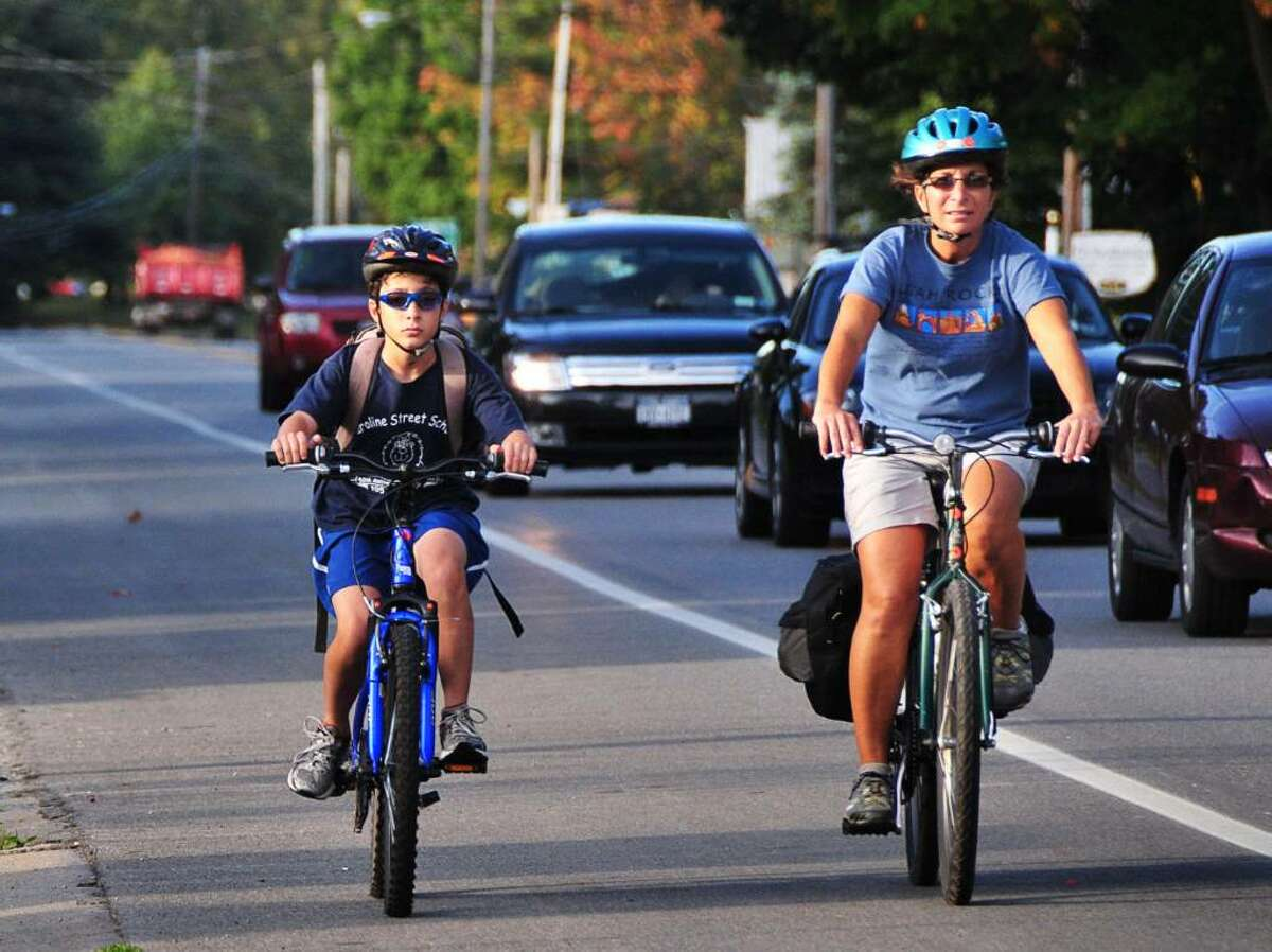 Student Adam Marino, left, 12, rides his bike home from school Thursday afternoon Sept. 24, 2009, accompanied by his mother, Janette Kaddo Marino. (John Carl D'Annibale / Times Union)