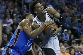 Oklahoma City Thunder guard Josh Huestis, left, grabs the ball held by San Antonio Spurs guard Dejounte Murray, right, and forces a jump ball in the first half of an NBA basketball game in Oklahoma City, Saturday, March 10, 2018. (AP Photo/Sue Ogrocki)