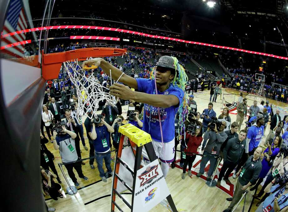 Kansas' Devonte' Graham cuts down the nets after the No. 9 Jayhawks beat 18th-ranked West Virginia in Saturday's Big 12 Tournament final at Kansas City, Mo. Photo: Charlie Riedel, STF / Copyright 2018 The Associated Press. All rights reserved.