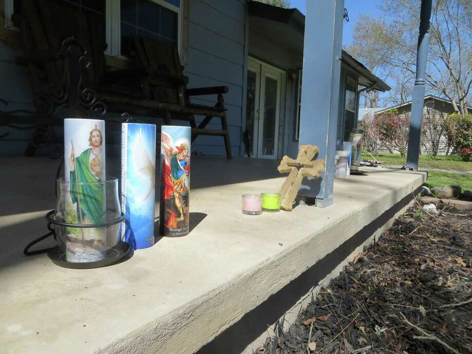 Candles and a cross stand on the porch of Anthony and Tiffany Strait's home in the Elm Grove subdivision about five blocks from where they were slain Feb. 25, 2018. Photo: Zeke MacCormack, San Antonio Express-News