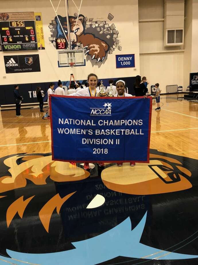 Midland Classical grad Kayla Beattie and Lee grad Daija Stanford hold the national title banner after Arlington Baptist beat Kentucky Christian, 63-59, in Saturday's NCCAA Division II national championship game in Greenville, S.C. Courtesy photo Photo: Courtesy Photo