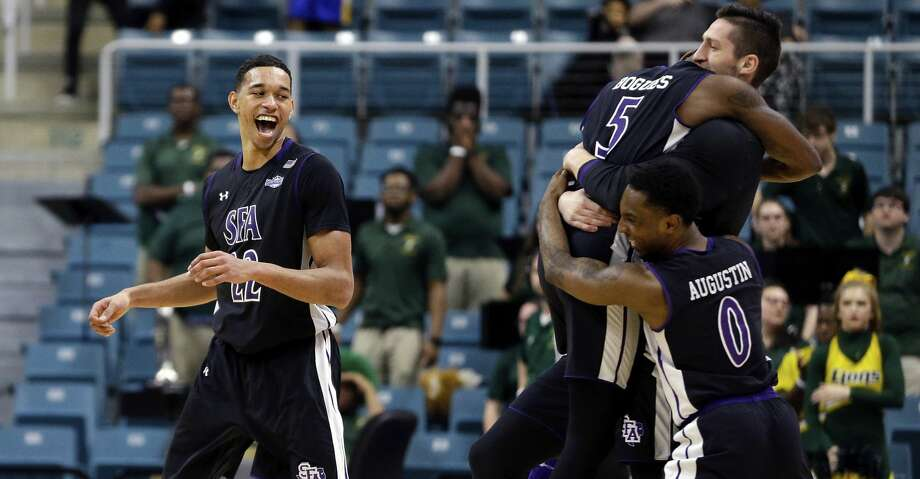 Stephen F. Austin forward TJ Holyfield (22) looks on as teammates Shannon Bogues (5) Aaron Augustin (0) and Jovan Grujic (32) embrace at mid court after defeating Southeastern Louisiana after an NCAA college basketball game in the Southland Conference's Men's Basketball Tournament Championship Saturday, March 10, 2018, in Houston. (AP Photo/Michael Wyke) Photo: Michael Wyke/Associated Press