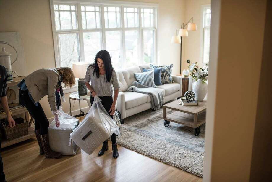 Kate Touhill and Dalana Caldwell, both of Staged to Sell & Design, unwrap ottomans for the living room of a single family home in Bryant on March 7, 2018. Photo: GRANT HINDSLEY, SEATTLEPI.COM / SEATTLEPI.COM