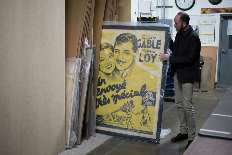 Jon Rosichelli showcases a vintage poster he plans to design a home around, in the warehouse at Rosichelli Design in Seattle on March 1, 2018. Photo: GRANT HINDSLEY, SEATTLEPI.COM / SEATTLEPI.COM