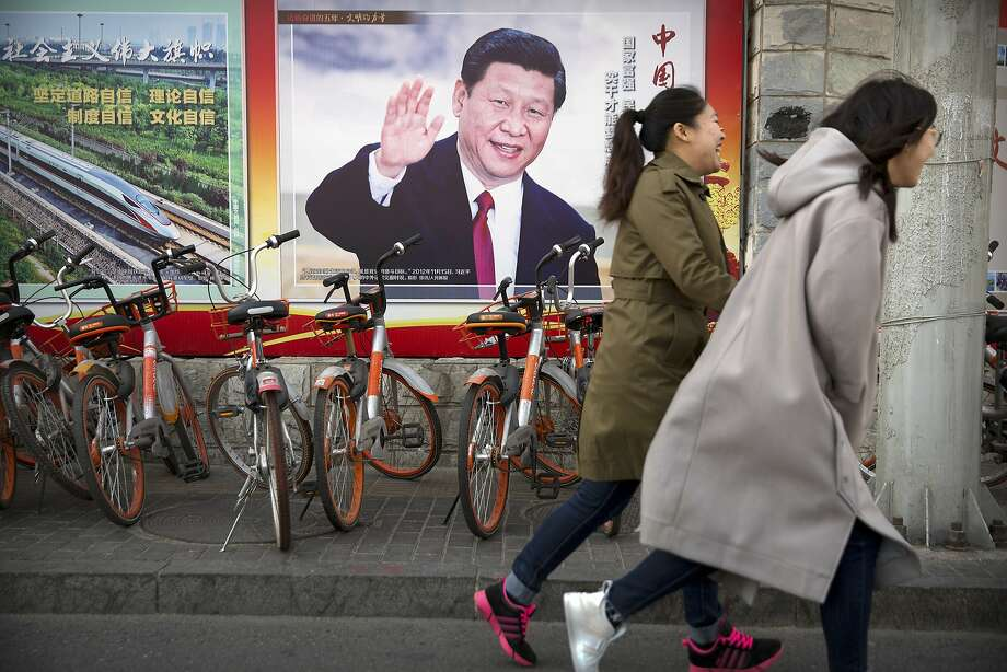 In this Friday, March 2, 2018, photo residents walk past a poster showing Chinese President Xi Jinping in Beijing. Xi, poised to rule over China indefinitely, is at the center of the Communist Party�s most colorful efforts to build a cult of personality since the death of the founder of the People's Republic, Mao Zedong, in 1976. (AP Photo/Mark Schiefelbein) Photo: Mark Schiefelbein, Associated Press