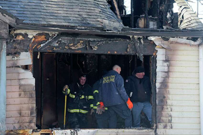 A view of the home at 900 Mann Ave., as the investigation continues into an early morning fire on Sunday, March 11, 2018, in Rensselaer, N.Y. The fire killed three people, including one child. Another child is in critical condition at a burn unit in Syracuse. (Paul Buckowski/Times Union)