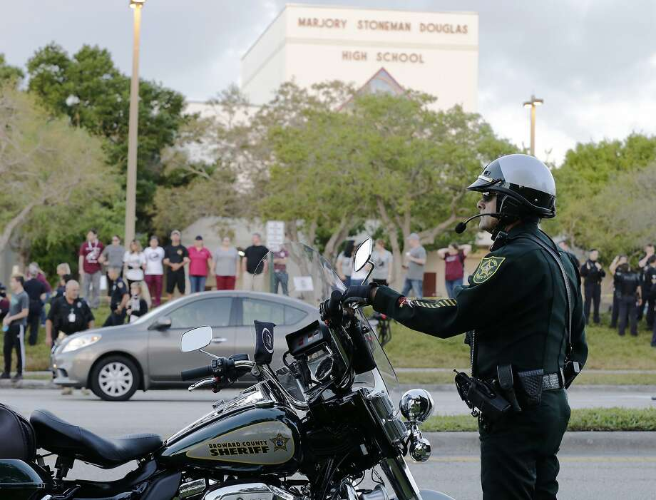 A police officer stands watch at Marjory Stoneman Douglas High School in Parkland, Fla., Wednesday, Feb. 28, 2018. Students returned to class for the first time since a former student opened fire there with an assault weapon. (AP Photo/Terry Renna) Photo: Terry Renna, Associated Press
