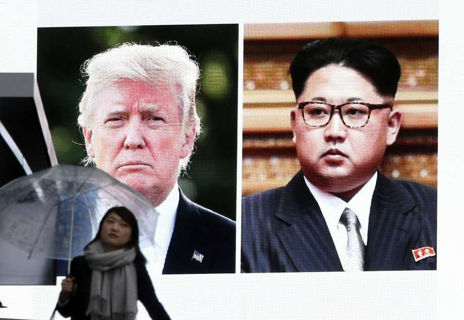 A woman walks by a huge screen showing U.S. President Donald Trump, left, and North Korea's leader Kim Jong Un, in Tokyo, Friday, March 9, 2018. After a year of threats and diatribes, U.S. President Donald Trump and third-generation North Korean dictator Kim Jong Un have agreed to meet face-to-face for talks about the North�s nuclear program.(AP Photo/Koji Sasahara) Photo: Koji Sasahara, Associated Press