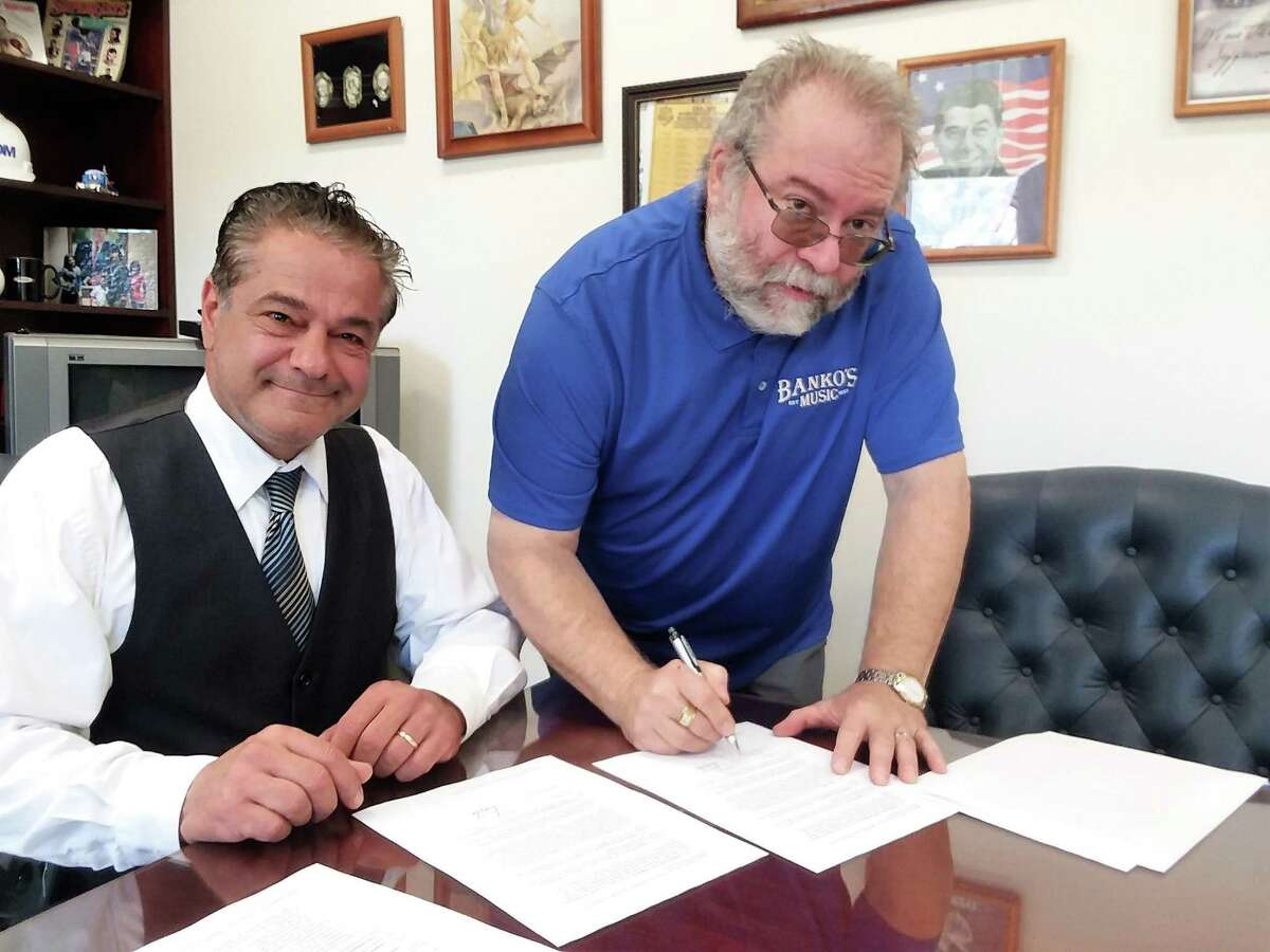 Ansonia Mayor David Cassetti, left, watches as Banko's owner Joe Shapiro signs a contract to operate the Rock the Summer free music concert at Nolan Field on July 28