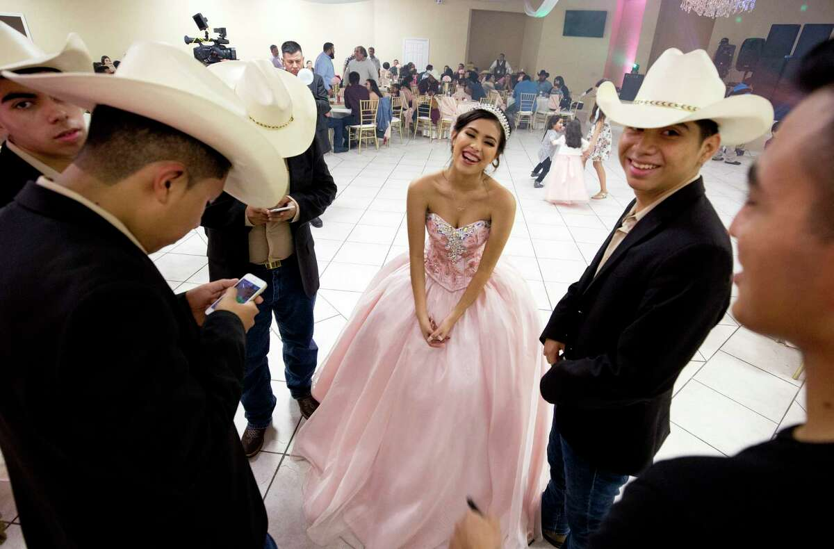 Fifteen-year-old Lizbeth Gutierrez, center, jokes with her chambelanes as they wait for her quinceañera to start at Monte Bello Reception Hall Saturday, Dec. 16, 2017, in Pasadena, Texas.