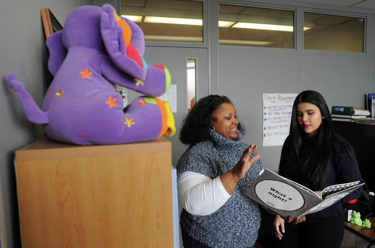 Natisha Vidal, a teen pregnancy social worker at Harding High School, shows Moyry Ramos, right, the book she should to read to her 2-year-old daughter as part of the early literacy program, Raising Readers, while the two met at the school in Bridgeport on Friday.