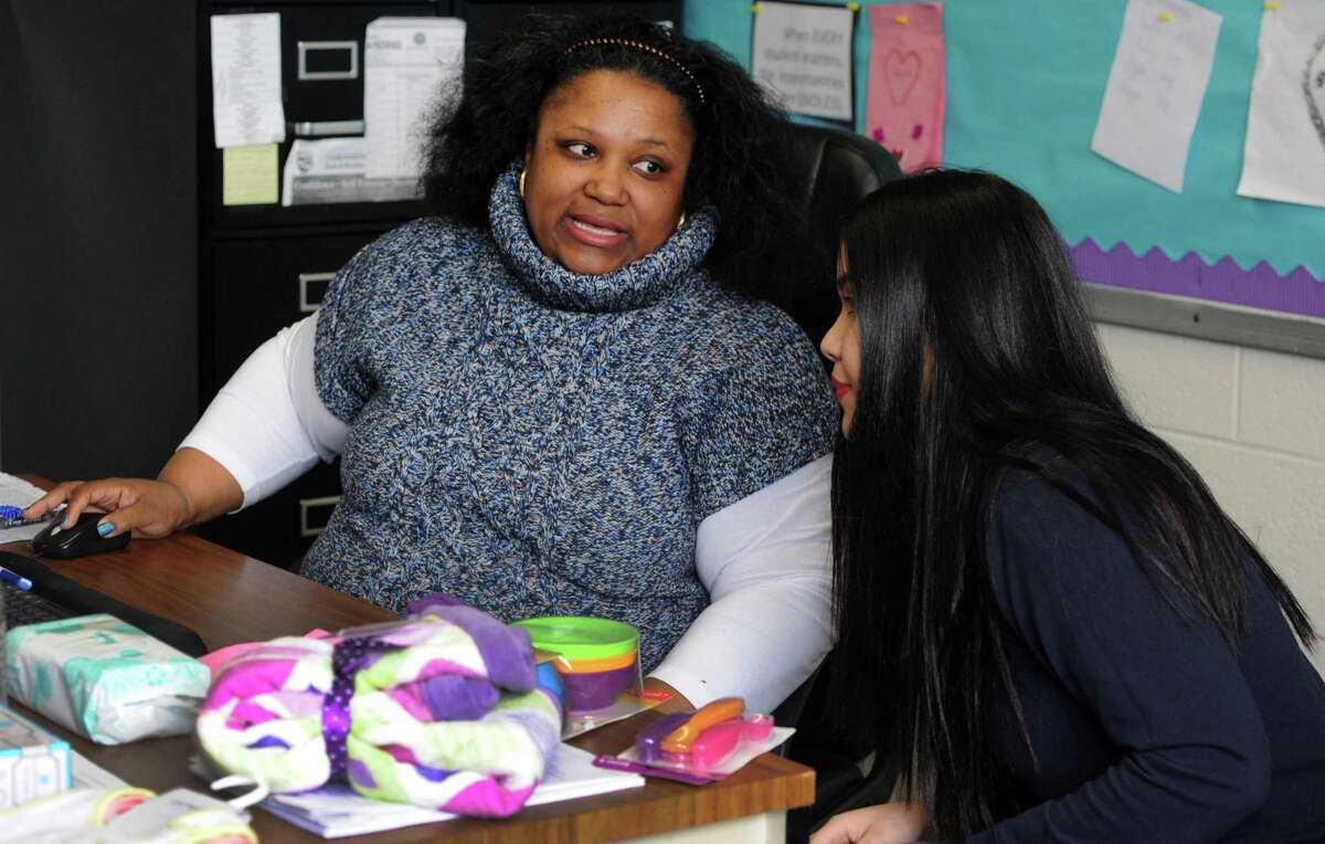 Natisha Vidal, a social worker at Harding High School, and Moyry Ramos, right, go over grades while the two meet at the school in Bridgeport on Friday. Ramos has a 2-year-old daughter she plans to enroll in the Early Learning Center day care planned at the new Harding High School when it opens next fall.
