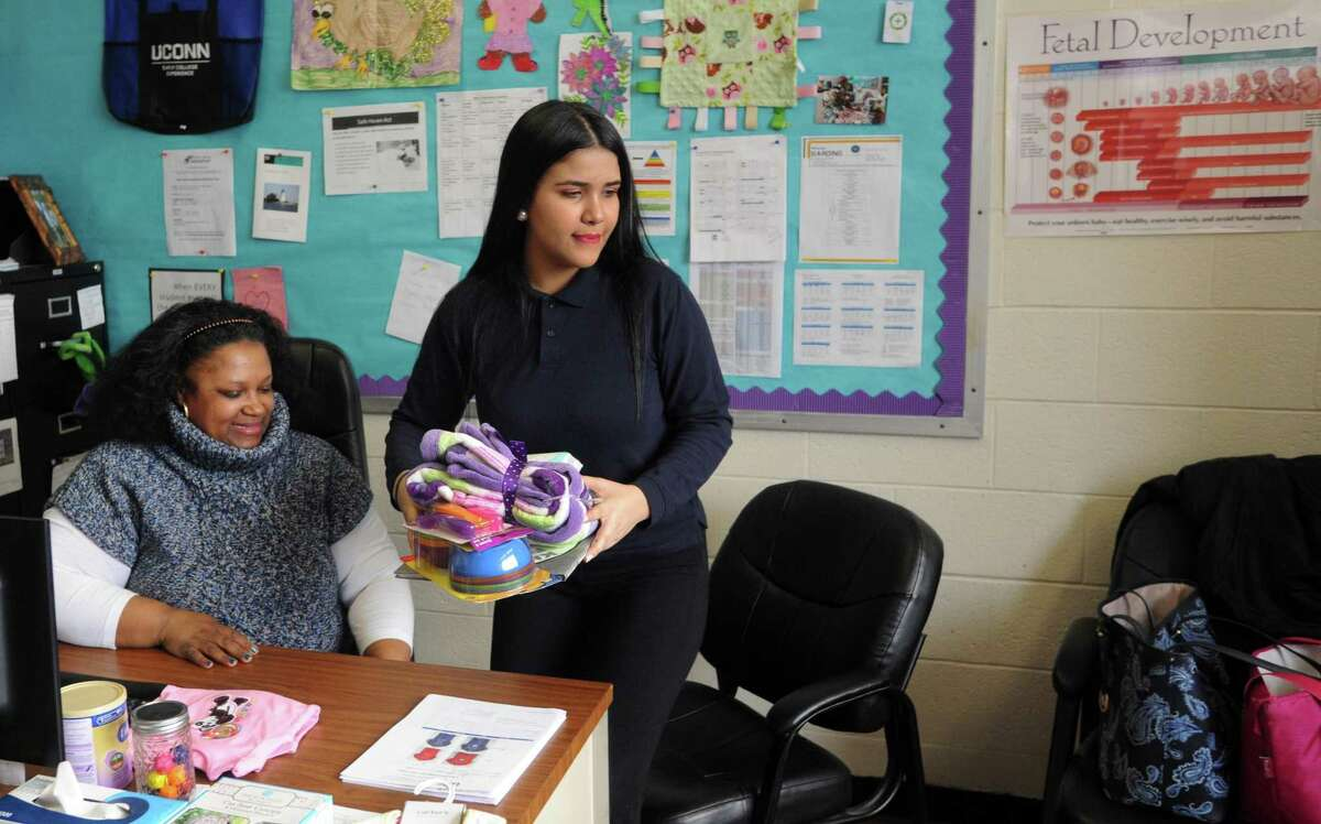 Moyry Ramos, right, a junior at Harding High School, packs up some items given to her after meeting with Natisha Vidal, a teen pregnancy social worker at Harding High School in Bridgeport, Conn. on Friday, March 9, 2018. Ramos plans to enroll her 2-year-old daughter in the Early Learning Center day care planned at the new Harding High School when it opens next fall.