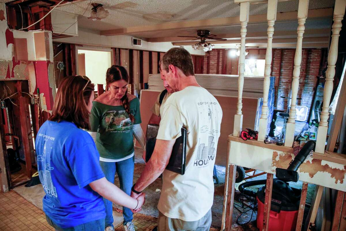 Homeowner Tracy Scoggins, second from left, tears up as she prays with Eight Days of Hope volunteers in her gutted kitchen Saturday, March 10, 2018 in Dickenson. Thousands of volunteers spread out across the Houston area to help more than 500 homeowners repair or rebuild their homes in the wake of Hurricane Harvey.