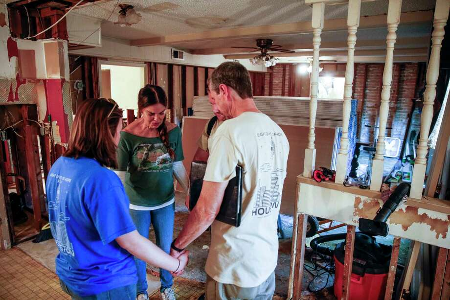Homeowner Tracy Scoggins, second from left, tears up as she prays with Eight Days of Hope volunteers in her gutted kitchen Saturday, March 10, 2018 in Dickenson. Thousands of volunteers spread out across the Houston area to help more than 500 homeowners repair or rebuild their homes in the wake of Hurricane Harvey. Photo: Michael Ciaglo, Houston Chronicle / Michael Ciaglo