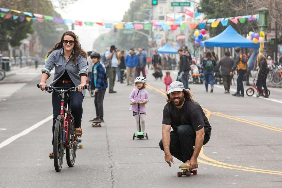 "Kurt Carpenter rides on a skateboard beside his girlfriend Molly Baldridge, riding a bike, at the Sunday Streets event on Valencia street. ""We look forward to this event each year."" Kurt says and adds ""It should be like this all the time."" March 11, 2018, San Francisco. Photo: Jana A�enbrennerov�, Special To The Chronicle"