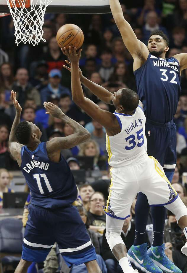 Golden State Warriors' Kevin Durant, center, shoots between Minnesota Timberwolves' Jamal Crawford, left, and Karl-Anthony Towns in the first half of an NBA basketball game Sunday, March 11, 2018, in Minneapolis. (AP Photo/Jim Mone) Photo: Jim Mone, Associated Press