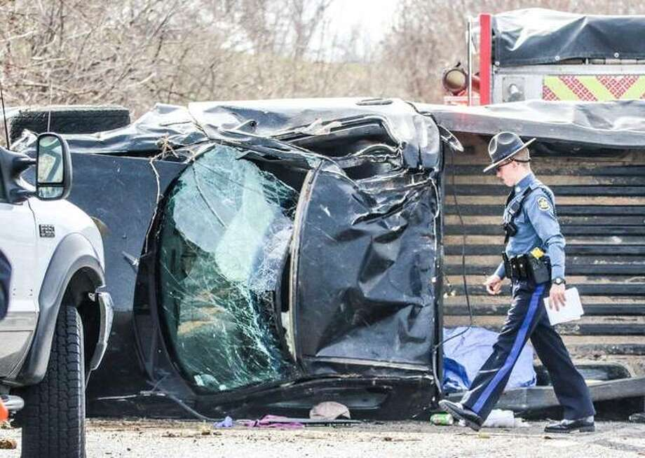 A trooper with the Missouri State Highway Patrol examines the Ford F-150 involved in an accident Saturday on U.S. Route 67 in West Alton, Missouri that injured a St. Louis man, who was initially pinned inside the overturned truck. Photo: Nathan Woodside | For The Telegraph