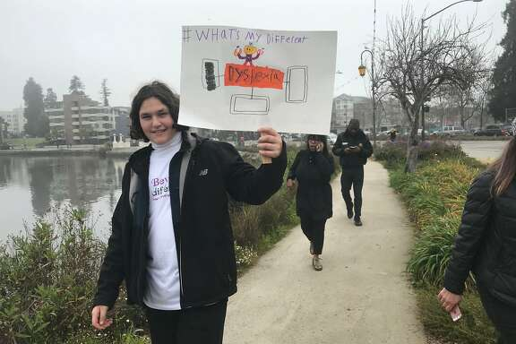 Omree Sabo, a 17-year-old student at Bayhill High School in Berkeley holds up a sign that identifies her as having dyslexia. Sabo marched with other students as part of a march organized by nonprofit Beyond Differences on March 11 at Lake Merritt.