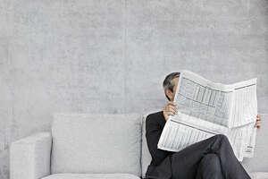 Man reading newspaper on sofa