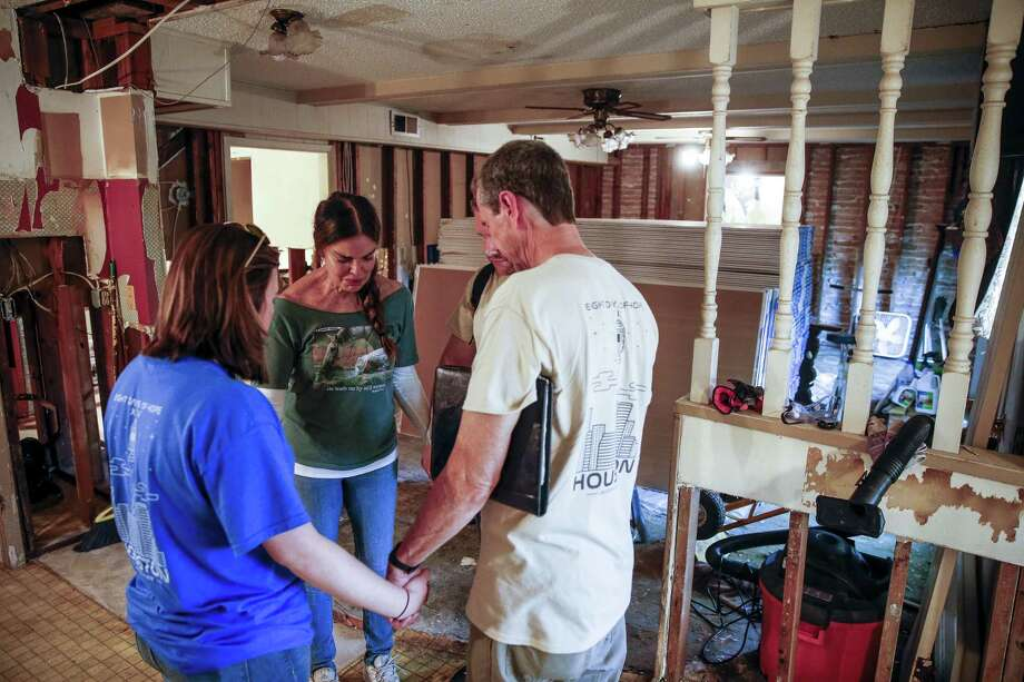 Homeowner Tracy Scoggins, second from left, tears up as she prays with Eight Days of Hope volunteers in her gutted kitchen Saturday, March 10, 2018 in Dickenson. Thousands of volunteers spread out across the Houston area to help more than 500 homeowners repair or rebuild their homes in the wake of Hurricane Harvey. (Michael Ciaglo / Houston Chronicle) Photo: Michael Ciaglo, Houston Chronicle / Houston Chronicle / Michael Ciaglo