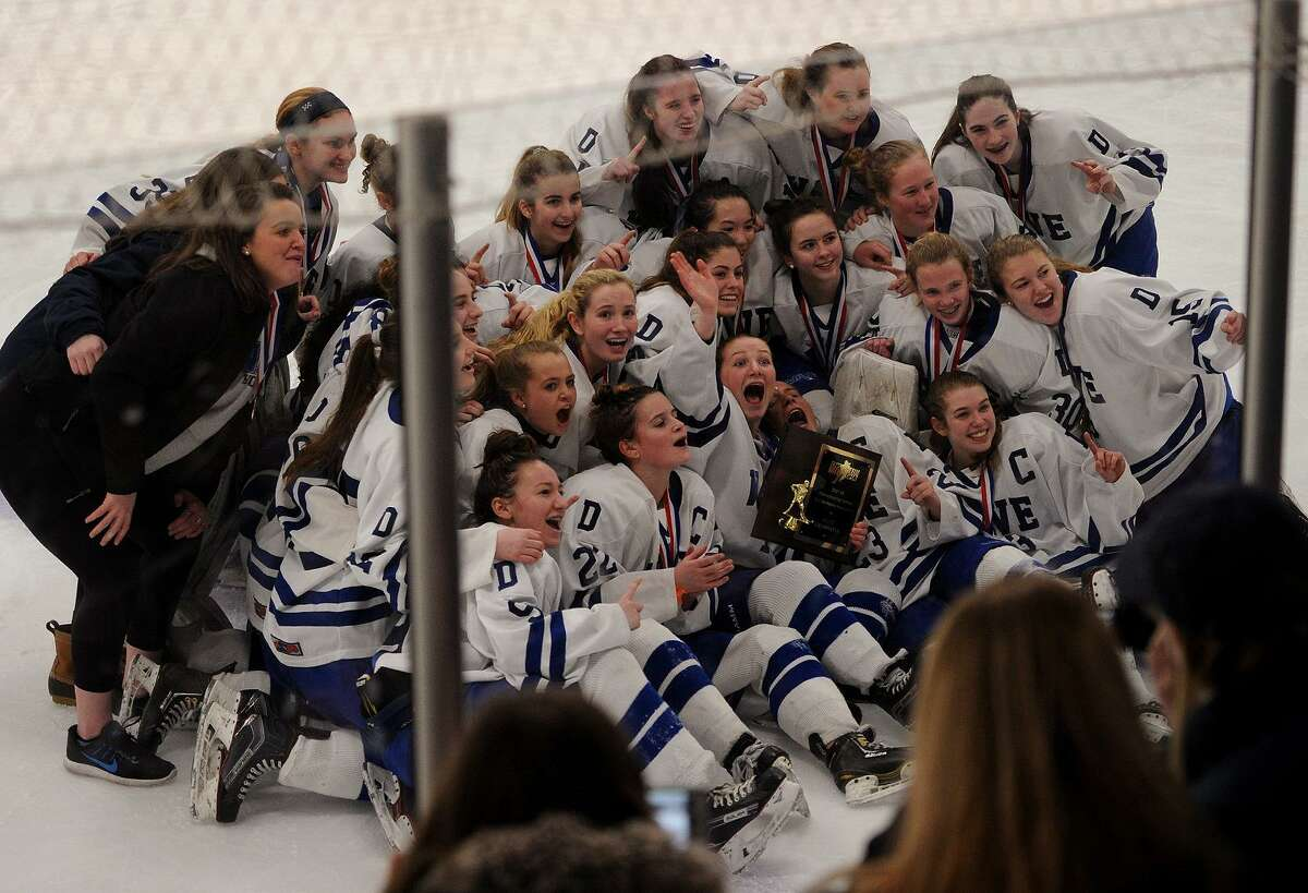 Darien's girls hockey team poses with the trophy following their 5-2 Girls Hockey Championship victory over Suffield Co-Op at Bennett Rink in West Haven, Conn. on Sunday, March 11, 2018.