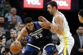 Minnesota Timberwolves' Karl-Anthony Towns, left, works his way around Golden State Warriors' Zaza Pachulia in the second half of an NBA basketball game Sunday, March 11, 2018, in Minneapolis. (AP Photo/Jim Mone)