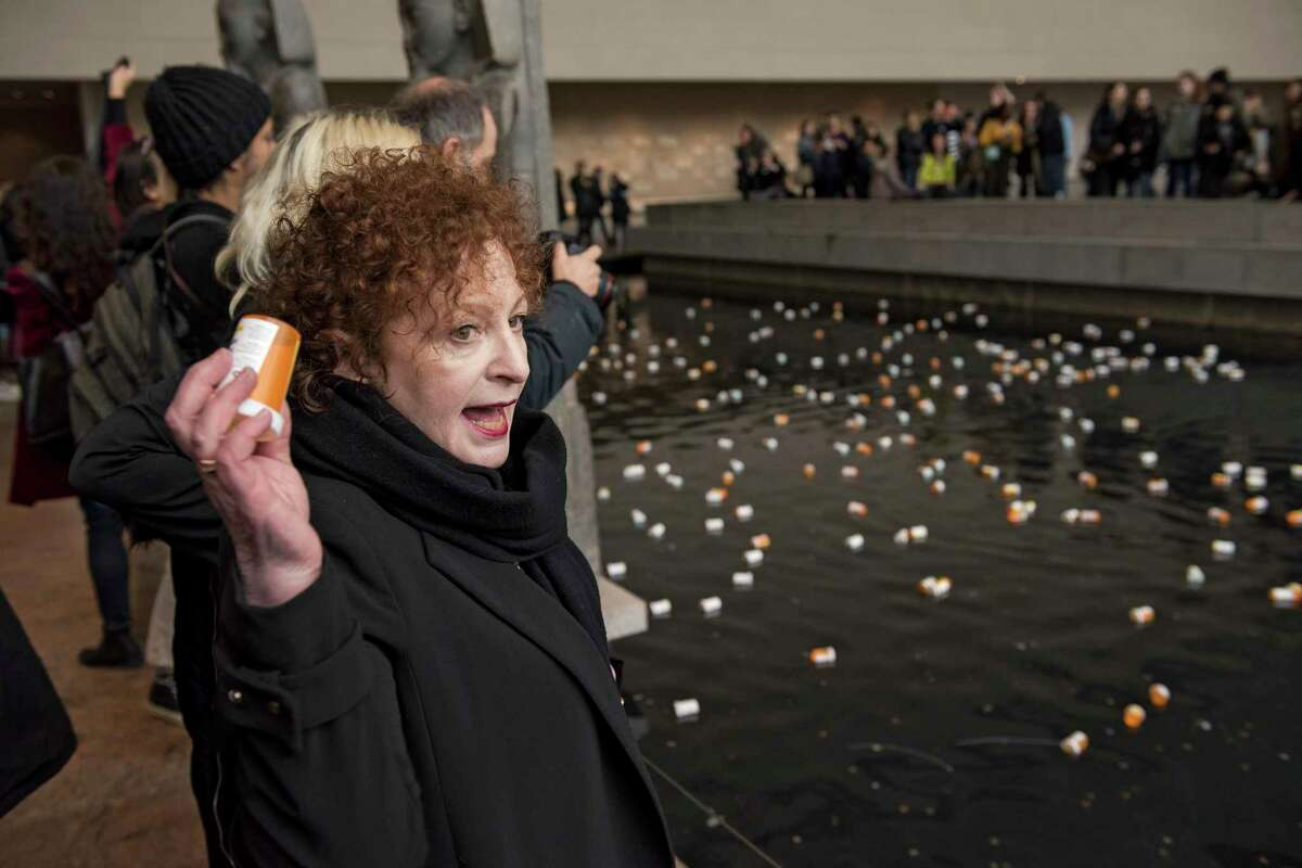 Photographer Nan Goldin leads a group protesting, in part by throwing prescription bottles into a reflecting pool in the Sackler Wing of the Metropolitan Museum of Art -- named for a family connected to the sales and marketing of OxyContin -- in New York, March 10, 2018. the protesters called for cultural institutions to reject money from the Sackler family and demanded, among other things, that Purdue Pharma, which has been accused of using deceptive and aggressive tactics to market OxyContin, fund addiction treatment. (George Etheredge/The New York Times)