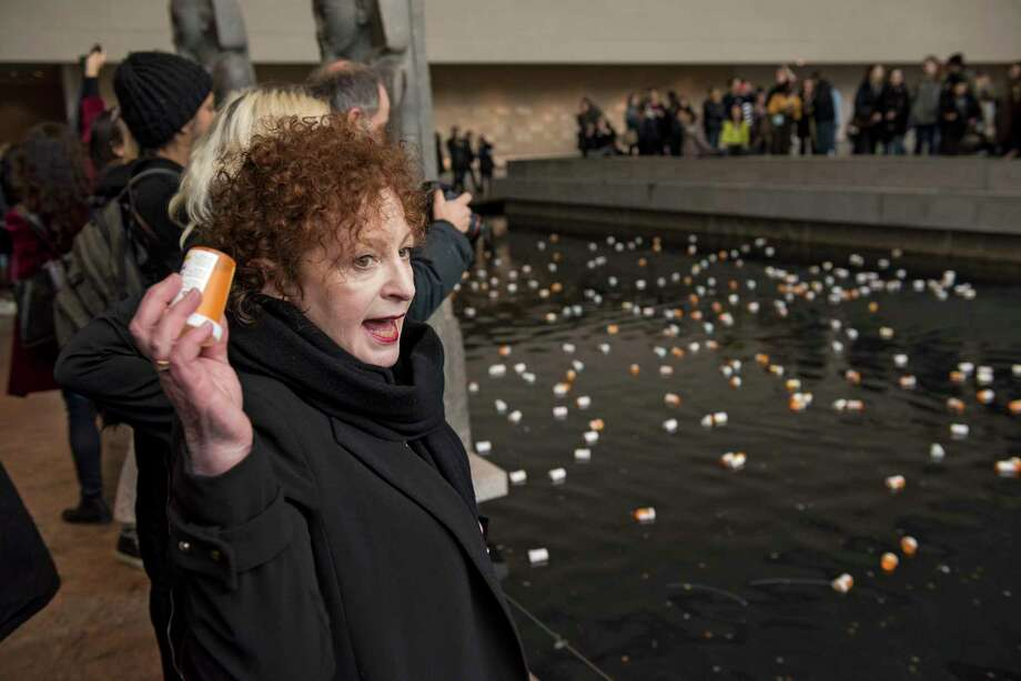 Photographer Nan Goldin leads a group protesting, in part by throwing prescription bottles into a reflecting pool in the Sackler Wing of the Metropolitan Museum of Art -- named for a family connected to the sales and marketing of OxyContin -- in New York, March 10, 2018. the protesters called for cultural institutions to reject money from the Sackler family and demanded, among other things, that Purdue Pharma, which has been accused of using deceptive and aggressive tactics to market OxyContin, fund addiction treatment. (George Etheredge/The New York Times) Photo: GEORGE ETHEREDGE / NYTNS