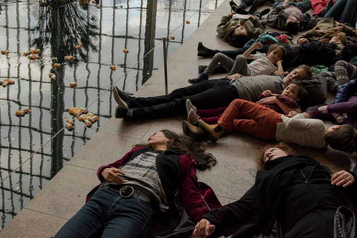 Protesters, including organizer Nan Goldin, bottom right, lay down by a reflecting pool into which they tossed prescription bottles at the Sackler Wing of the Metropolitan Museum of Art, which is named for a family connected to the sales and marketing of OxyContin, in New York, March 10, 2018. The protesters called for cultural institutions to reject money from the Sackler family and demanded, among other things, that Purdue Pharma, which has been accused of using deceptive and aggressive tactics to market OxyContin, fund addiction treatment. (George Etheredge/The New York Times)