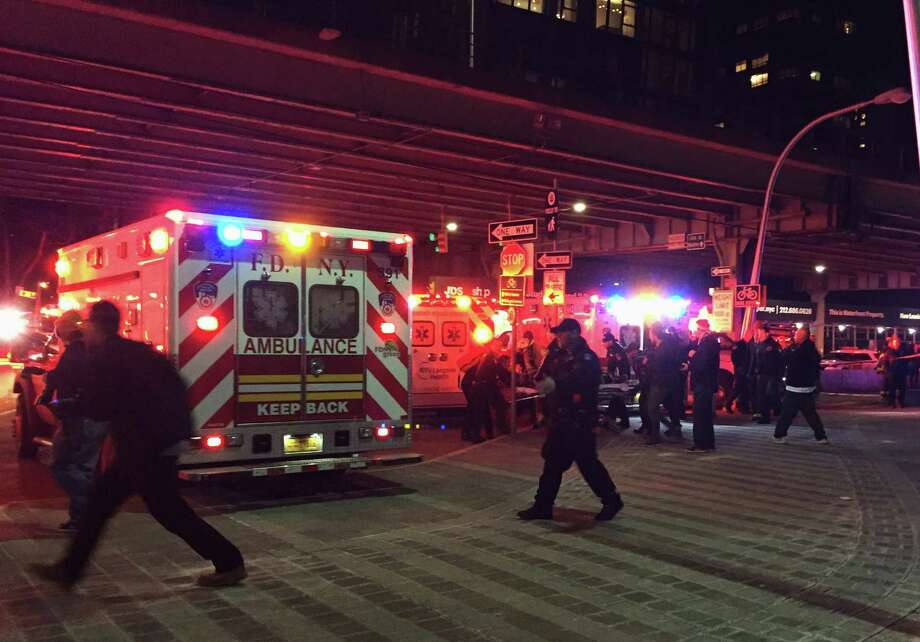 "First responders carry a person to an ambulance after a helicopter crashed into the East River along New York on Sunday, March 11, 2018. A Federal Aviation Administration spokeswoman said Sunday the Eurocopter AS350 went down just after 7 p.m. Sunday in the waterway just north of Roosevelt Island and is ""reportedly inverted in the water."" Photo: Jennifer Peltz, AP / AP"