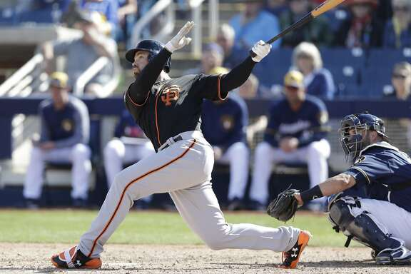 San Francisco Giants' Mac Williamson follows through on his three-run home run during the fifth inning of a spring training baseball game against the Milwaukee Brewers, Wednesday, Feb. 28, 2018, in Maryvale, Ariz. (AP Photo/Carlos Osorio)