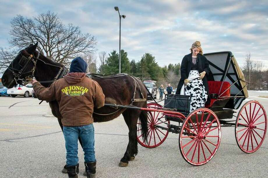 Arriving in style 				As her father, Clay DeJongh, holds the horse, Havahna DeJongh, 13, of Coleman, gets out of the horse-drawn buggy she took to the Blizzard Ball on Saturday at Coleman High School. The buggy belonged to her great-great-grandfather, Albert Fike; the horse belongs to family friend Henry Miller of Beaverton. (Danielle McGrew Tenbusch/for the Daily News) / ©2018