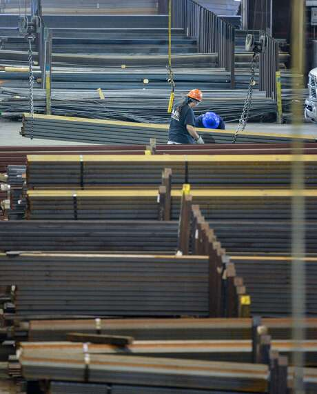 Workers move material at Alamo Iron Works in San Antonio. Texas factories cut production growth by more than half this month as local executives warned that the Trump administration's steel and aluminum tariffs will hike costs and squeeze profits this year, according to the Dallas Fed. Photo: Robin Jerstad /For The San Antonio Express-News