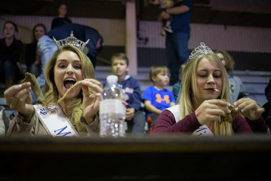 'Miss Texas' Margana Wood (L) and 'Miss Snake Charmer' Cyera Pieper compete in a rattlesnake-eating contest during the Sweetwater Rattlesnake Roundup at Nolan County Coliseum on March 11, 2018 in Sweetwater, Texas. Photo: AFP Contributor/AFP/Getty Images
