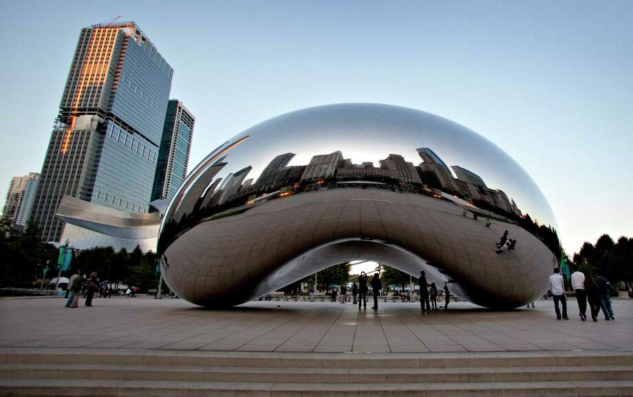 "The Chicago skyline is reflected in the polished metal surface of Anish Kapoor's ""Cloud Gate"" sculpture in Millenniun Park in Chicago. Photo: Bloomberg Photo By John Zich / © Bloomberg Finance LP"