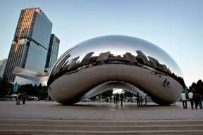 "The Chicago skyline is reflected in the polished metal surface of Anish Kapoor's ""Cloud Gate"" sculpture in Millenniun Park in Chicago."
