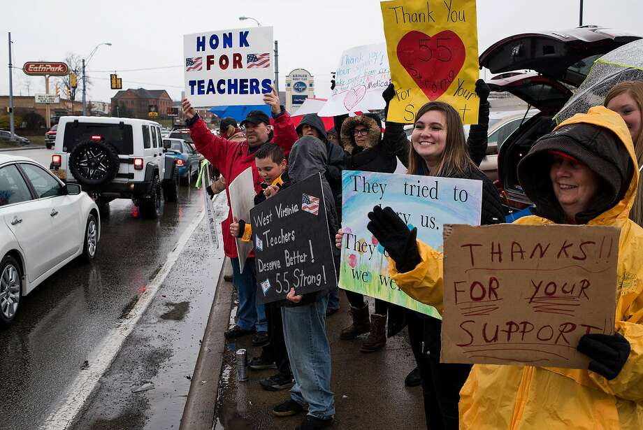 Educators and students hold signs in support of a statewide teacher strike in Morgantown, W.Va., last Tuesday. Teachers in the state got a 5 percent raise after a nine-day walkout. Photo: TY WRIGHT, NYT