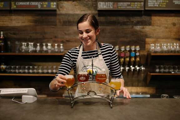 Haley Meace serves up a sampler at the Secret Trail Brewing in Chico, Calif., Saturday, March 3, 2018.