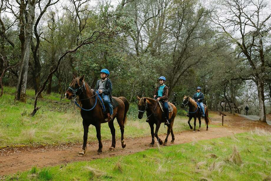 From the left, Ryan Kohler, 10, Katey Kohler, 13, Greta Kohler ride their horse through the trails at Loafer Creek Recreation Area on Lake Oroville. Photo: Mason Trinca, Special To The Chronicle