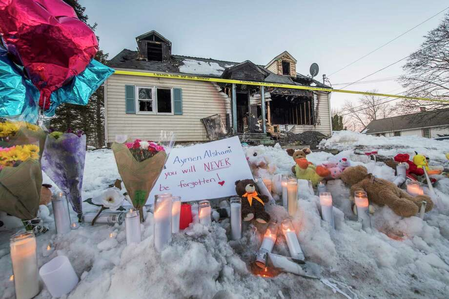 A makeshift memorial was set up in front of the burned out shell of a home which is all that is left of 900 Mann Avenue Monday March 12, 2018 after two adults and one child lost their lives in a multi-alarm fire which occurred early Sunday morning  in Rensselaer, N.Y. (Skip Dickstein/Times Union) Photo: SKIP DICKSTEIN, Albany Times Union