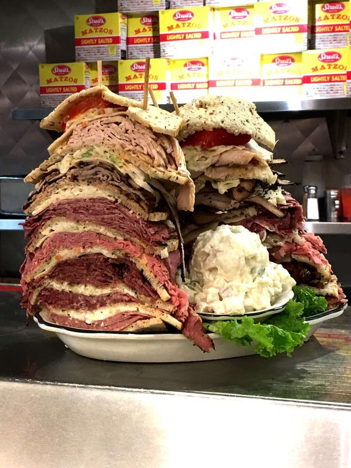 Where: Kenny & Ziggy's New York DelicatessenChallenge: The Zellagabetsky - In one sitting, finish an eight-decker sandwich on rye with corned beef, pastrami, turkey roast beef, salami, tongue, and Swiss cheese. Sides include coleslaw and Russian dressing.Cost: $65.00Reward: A free slice of cheesecake. Photo source: Yelp / Cindy S.