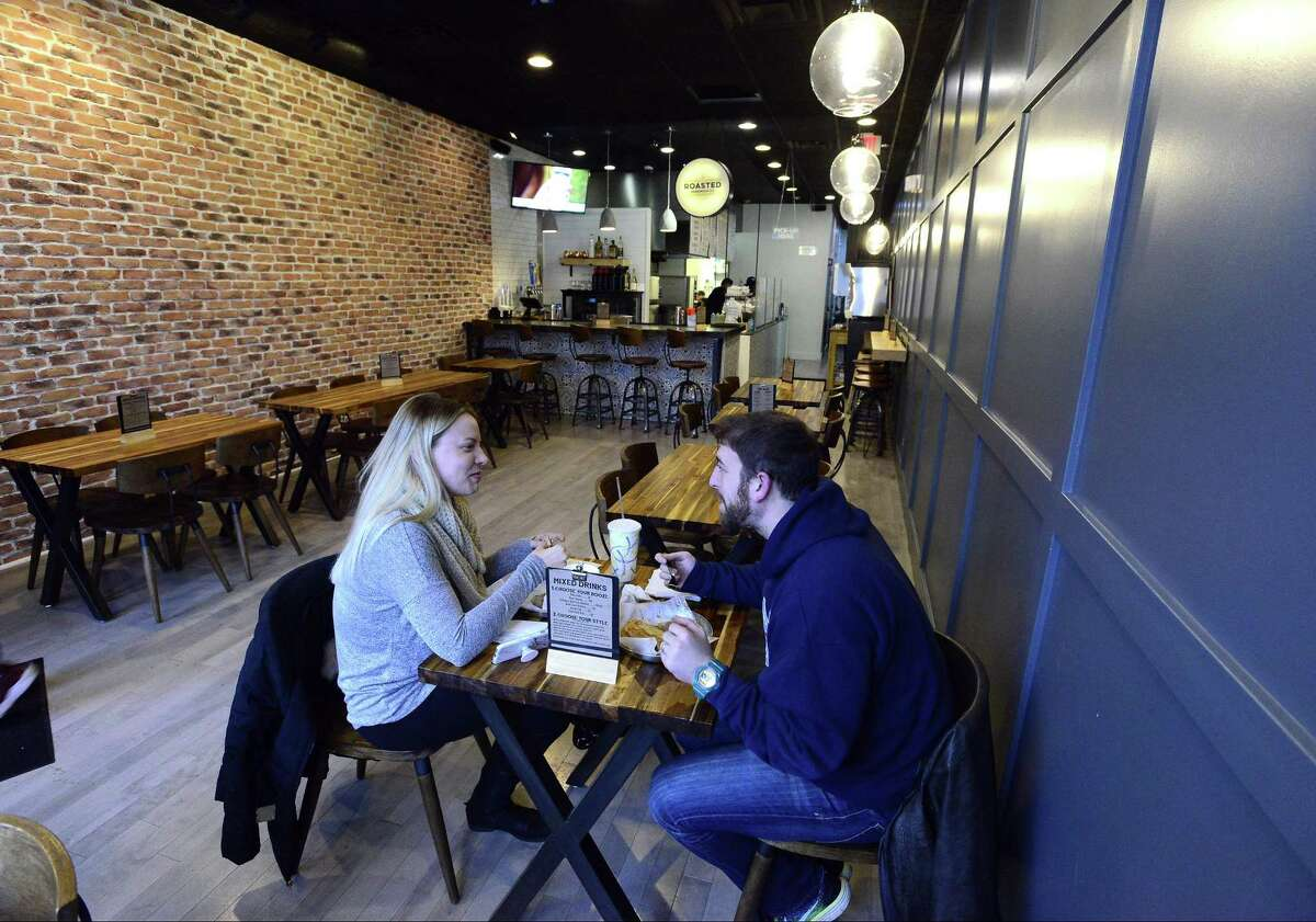 A pair of customers enjoy their meal at the new Roasted Sandwich Co., at 148 Bedford St., in Stamford, Conn., on Thursday, March 8, 2018.