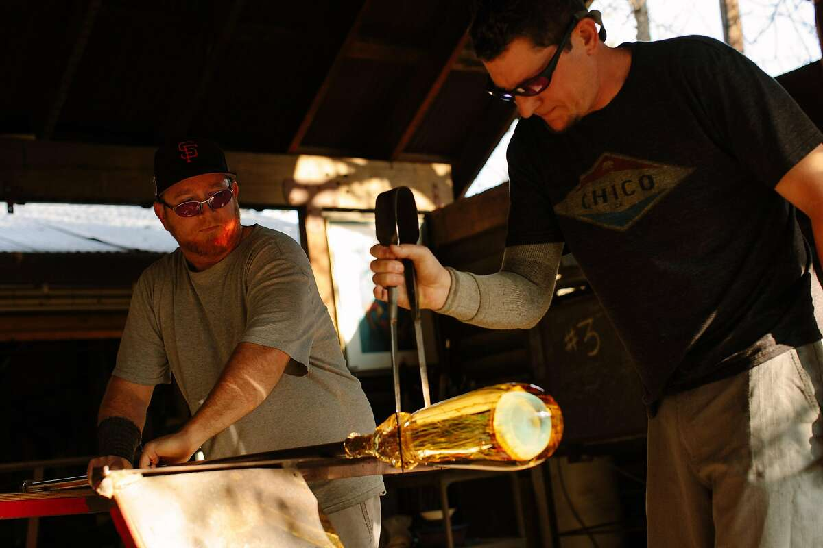 Wyatt Campbell and Mark Del Fava shapes the glass at the Satava Art Glass studio in Chico, Calif., Saturday, March 3, 2018.