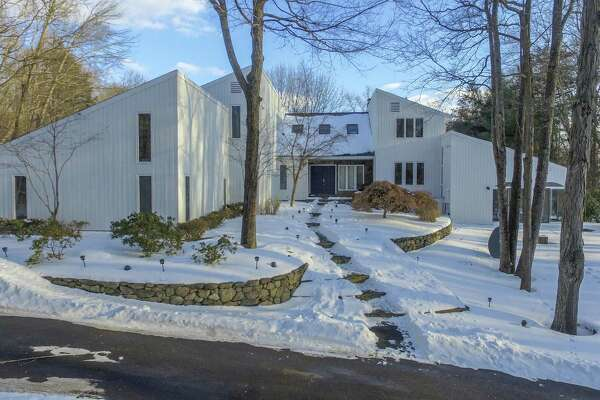 The contemporary house at 1 Winslow Road in Weston is like a spa/resort with an indoor swimming pool, sauna, exercise room, aerated pond, and immediate access to managed hiking trails and protected open space.